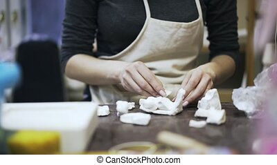 Woman putting pieces of gypsum - Close up of woman s hands...