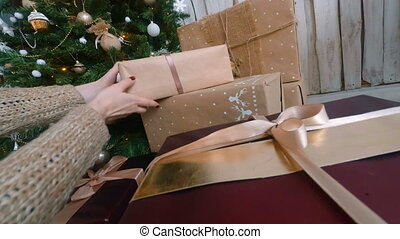 Woman putting presents under christmas tree