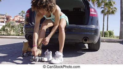 Woman putting roller skates - Young woman putting on roller...