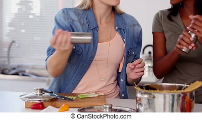 Woman putting salt and pepper in pot while cooking in the kitchen