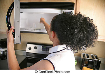 Woman putting something into microwave