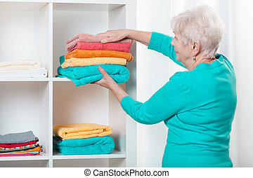 Woman putting towels to the shelf