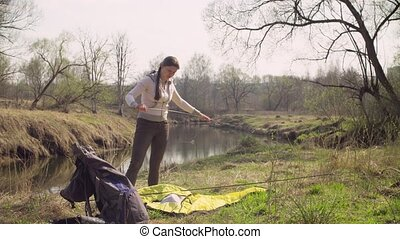 Woman putting up a tourist tent in the forest near the...