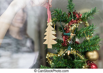 Woman putting up Christmas ornament at home holding a wooden tree in her hand