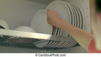 Woman putting white plates in dishwasher dryer - Woman opens...