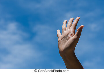 Woman raise hand up showing the five fingers on blue sky with white cloud background