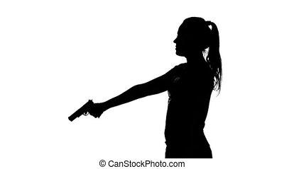 Woman raises the gun and blows the barrel. Silhouette. White...