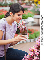 Woman raising a flower while smelling