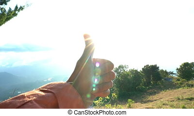 Woman raising hand with thumbs-up on clear blue sky...