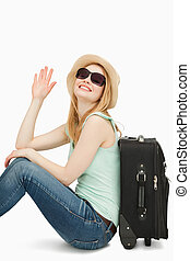 Woman raising her hand while sitting near a suitcase