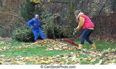 Woman rake leaves. Man do mess in garden yard. Playful couple. 4K
