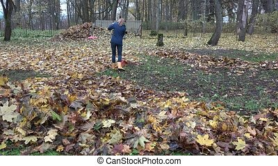 woman raking and composting leaves in autumn backyard. 4K