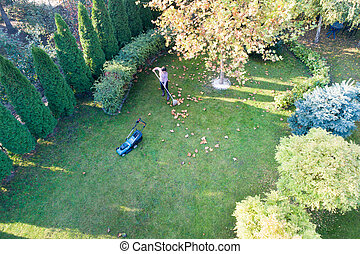 Woman raking leaves and trimming lawn