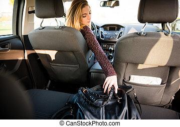Woman reaching handbag from back seat - Young woman reaching...