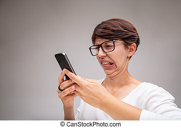 Woman reacting in revulsion to her mobile phone grimacing ...