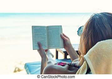 Woman reading a book at the beach