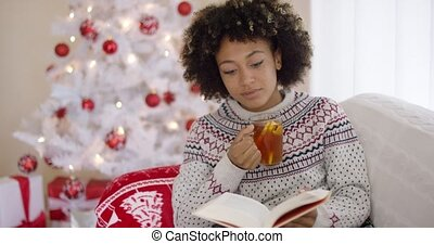 Woman reading a book in front of a Christmas tree