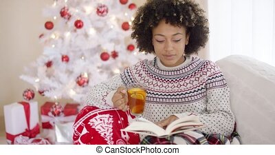 Woman reading a book in front of Christmas tree