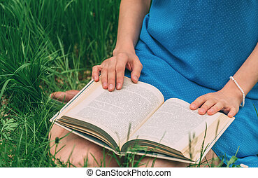 Woman reading a book in summer park
