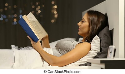 Side view of a relaxed woman reading a book in the night in the bed at home