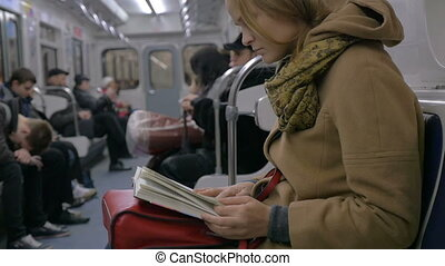 Slow motion shot of a woman sitting in tube train and reading a book.