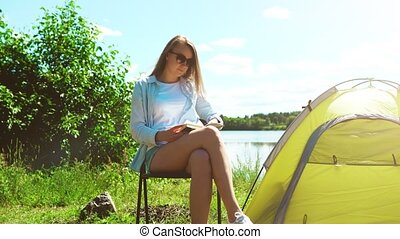 Woman reading a book near camping tent by the lake.