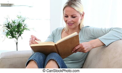 Woman reading a book on her sofa
