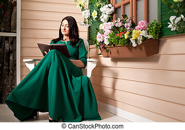 Woman reading a book on the veranda