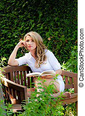 Woman reading a book in the garden