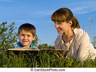 Woman, reading a book to the young boy in a green  meadow