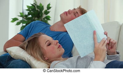 Woman reading a book while her boyfriend is napping