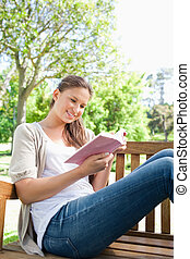 Woman reading a book while sitting on a bench
