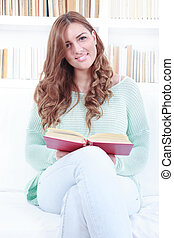 Woman reading a book while sitting on a white couch in a living room with library background behind her, domestic atmosphere.