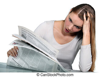 Woman reading a newspaper in shock