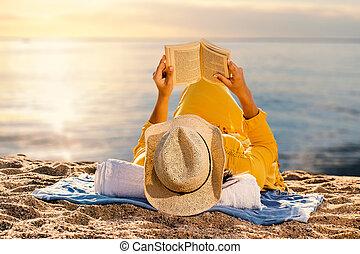Woman reading a novel at sunset on beach.