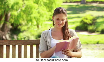 Woman reading a novel in a park while sitting on a bench