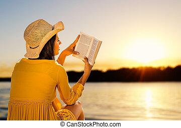Woman reading a novel on beach at sunset.