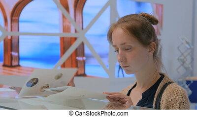 Woman reading advertisement brochure at urban exhibition