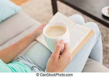 Woman reading and drinking coffee on couch
