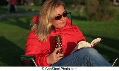 Woman reading and relaxing in park