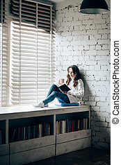 Woman reading book and drinking hot coffee sitting on window sill