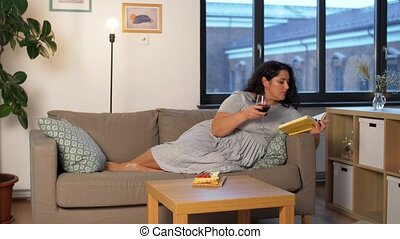 technology, leisure and people concept - happy smiling woman reading book and drinking red wine and eating snacks at home in evening