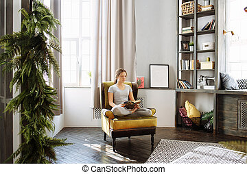 Woman reading book at home in the living room