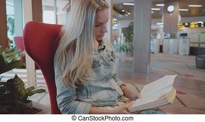 Woman reading book at the airport
