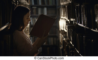 Woman reading book, dark library