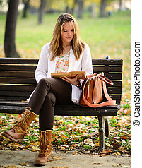 Woman reading book in the Autumn park