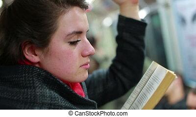 Woman reading book inside metro