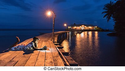 Woman reading book on a wooden warf at night . - Woman ...