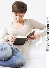 Woman reading book on sofa closeup
