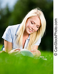 Woman reading book on the grass